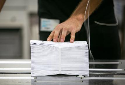 צילום תקריב של יד של מפעיל אורזת חבילת מעטפות